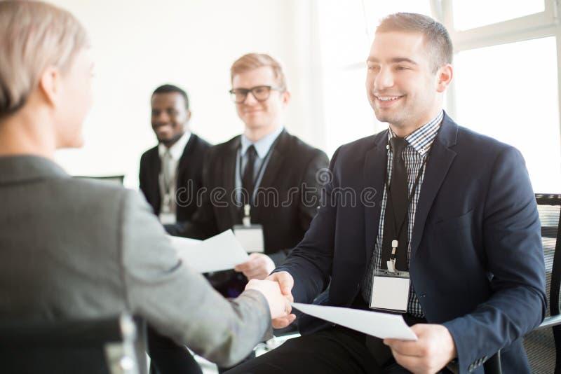 Colegas sonrientes que sacuden las manos en la reunión fotografía de archivo libre de regalías