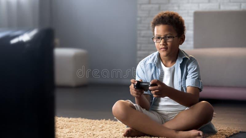 Colegial afroamericano que pasa su tiempo libre que juega a los juegos en la consola, ocio fotos de archivo libres de regalías