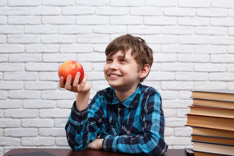 Colegial alegre sonriente con la manzana roja grande Consumición sana, s foto de archivo libre de regalías