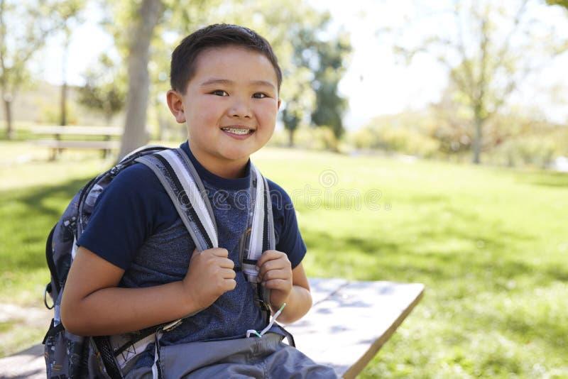 Colegial asiático joven con la mochila que sonríe a la cámara fotografía de archivo libre de regalías