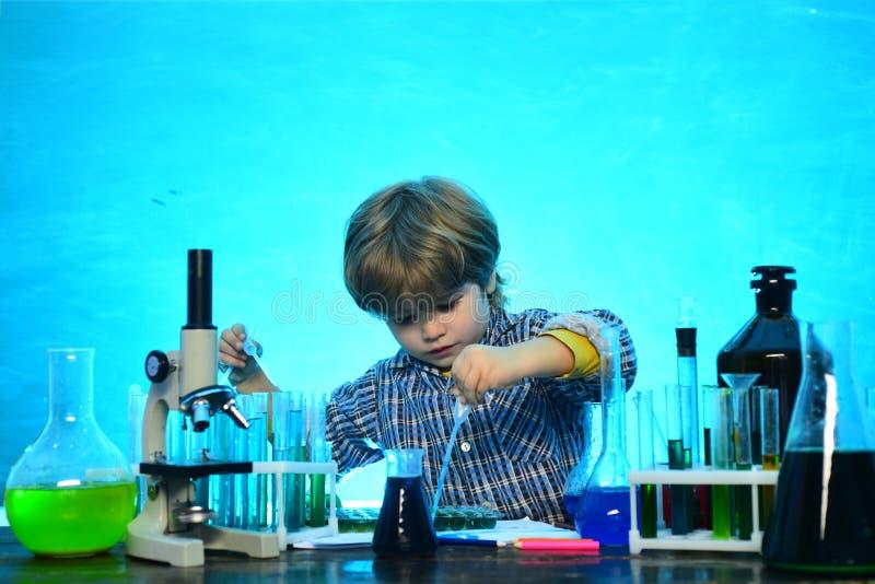 Colegial Concepto de la escuela Aliste para la escuela ciencia Ni?o peque?o sonriente alegre que se divierte contra la pared azul fotografía de archivo libre de regalías