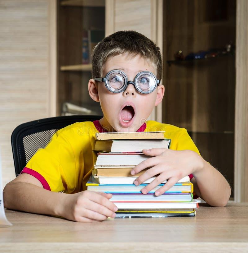 Colegial confuso en vidrios divertidos que grita cerca de la pila enorme de libros Educación imágenes de archivo libres de regalías