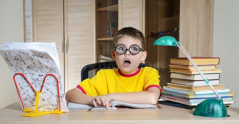 Colegial confuso en vidrios divertidos que grita cerca de la pila enorme de libros Educación Muchacho que tiene problemas con su  imágenes de archivo libres de regalías