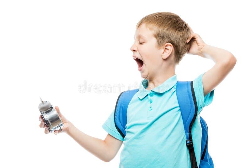 Colegial de bostezo cansado con un despertador fotografía de archivo