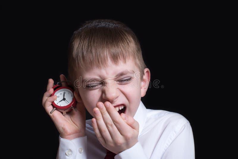 Colegial de bostezo con un despertador rojo en sus manos Concepto de la ma?ana Fondo negro imagen de archivo libre de regalías