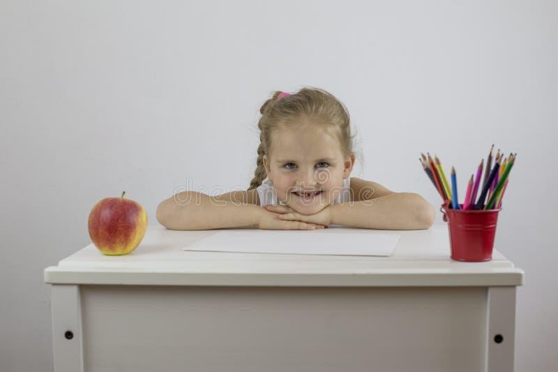 Colegial de la muchacha en su escritorio con miradas y sonrisas de los lápices fotos de archivo