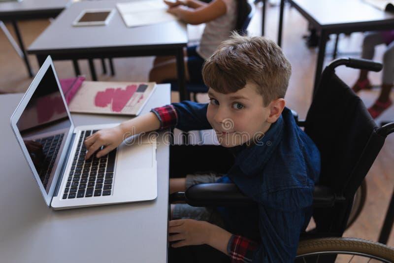 Colegial de la neutralización que estudia en el ordenador portátil mientras que se sienta en el escritorio en sala de clase fotografía de archivo libre de regalías