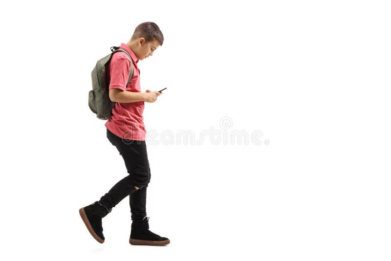 Colegial de moda que camina y que mira un teléfono móvil imagenes de archivo