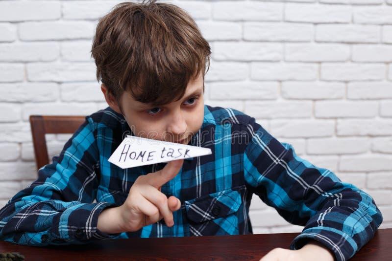 Colegial desobediente travieso que hace el avión de papel de su tas del hogar imagen de archivo libre de regalías