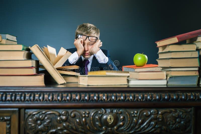 Colegial en la tensión o la depresión en la sala de clase de la escuela imagenes de archivo