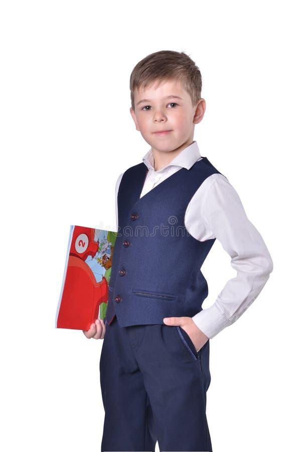 Colegial en traje azul en el fondo blanco con el libro en su mano foto de archivo libre de regalías