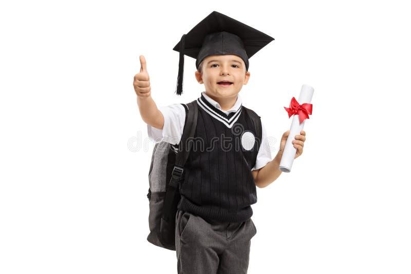 Colegial en un uniforme con el sombrero y el diploma de la graduación que hacen el pulgar encima del gesto imagen de archivo