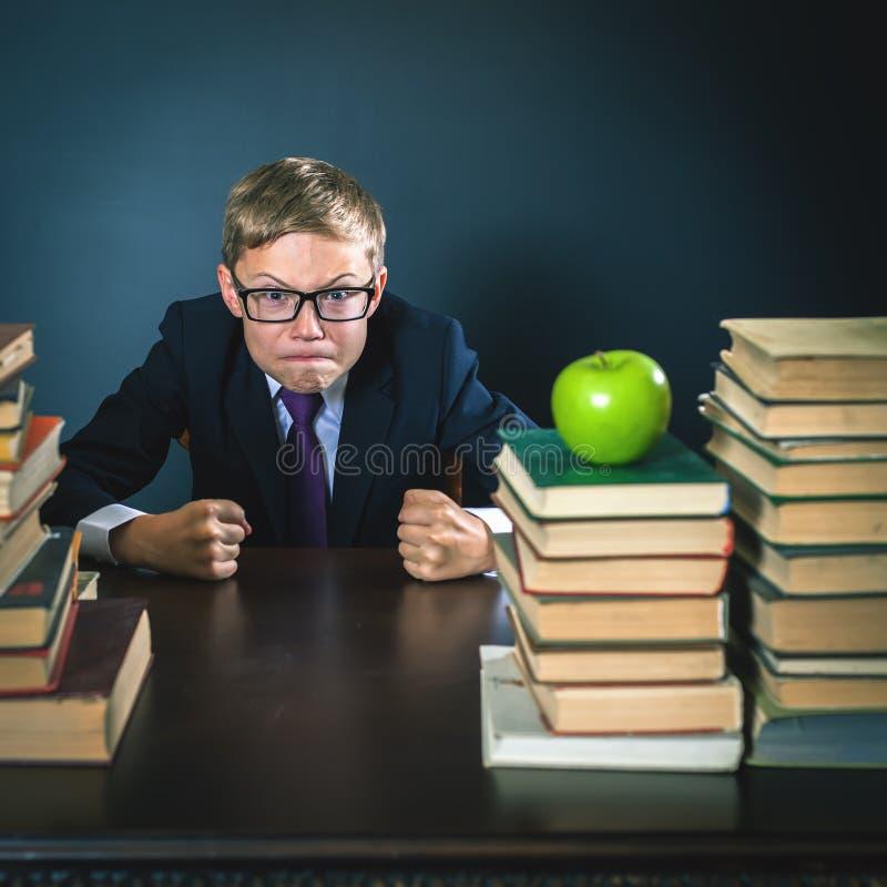 Colegial enojado en la tensión o la depresión en la sala de clase de la escuela imagen de archivo libre de regalías