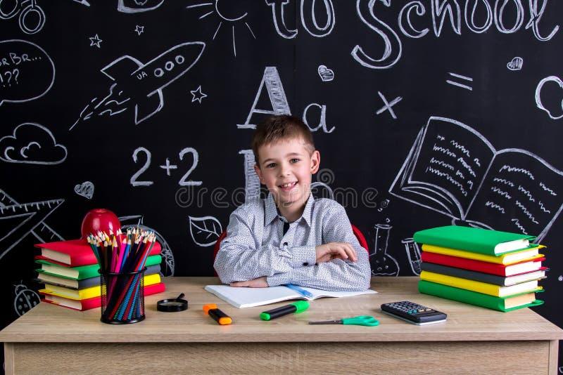 Colegial excelente feliz sonriente que se sienta en el escritorio con los libros, fuentes de escuela, con ambos brazos inclinados fotos de archivo libres de regalías