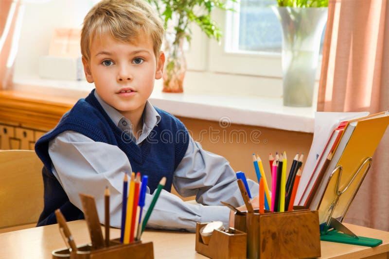 Colegial joven que se sienta detrás de un escritorio de la escuela foto de archivo
