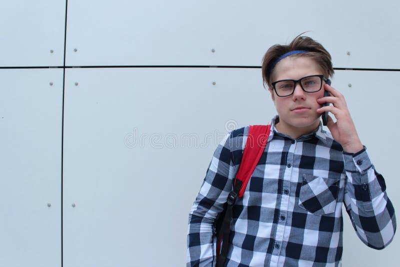 Colegial o estudiante del adolescente del muchacho en la camisa, sonriendo con los vidrios, mochila roja imagen de archivo libre de regalías