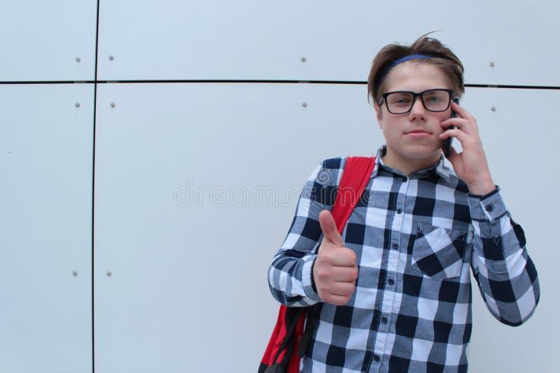 Colegial o estudiante del adolescente del muchacho en la camisa, sonriendo con los vidrios, mochila roja imagenes de archivo