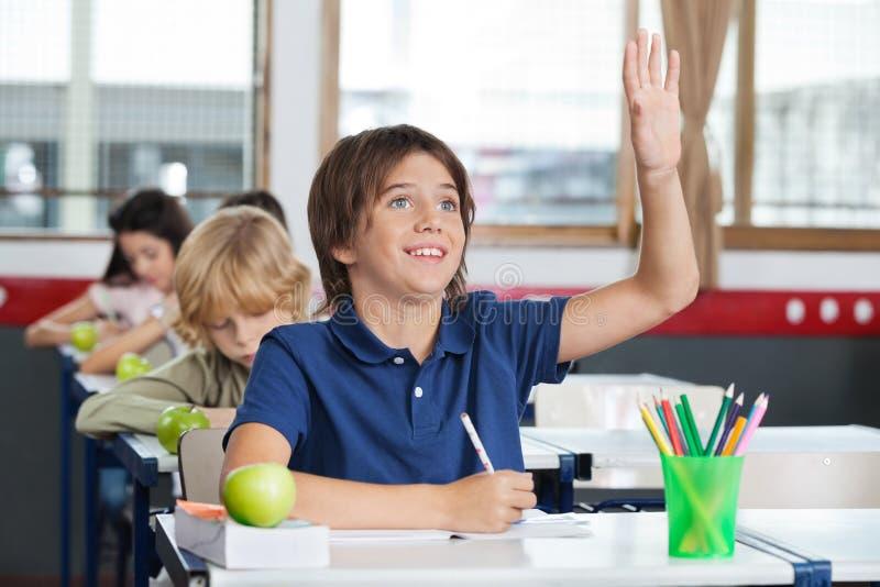Colegial que aumenta la mano mientras que se sienta en el escritorio fotografía de archivo