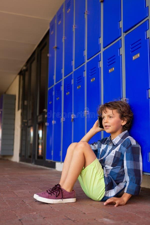 Colegial que habla en el teléfono móvil mientras que se sienta en el pasillo imagen de archivo