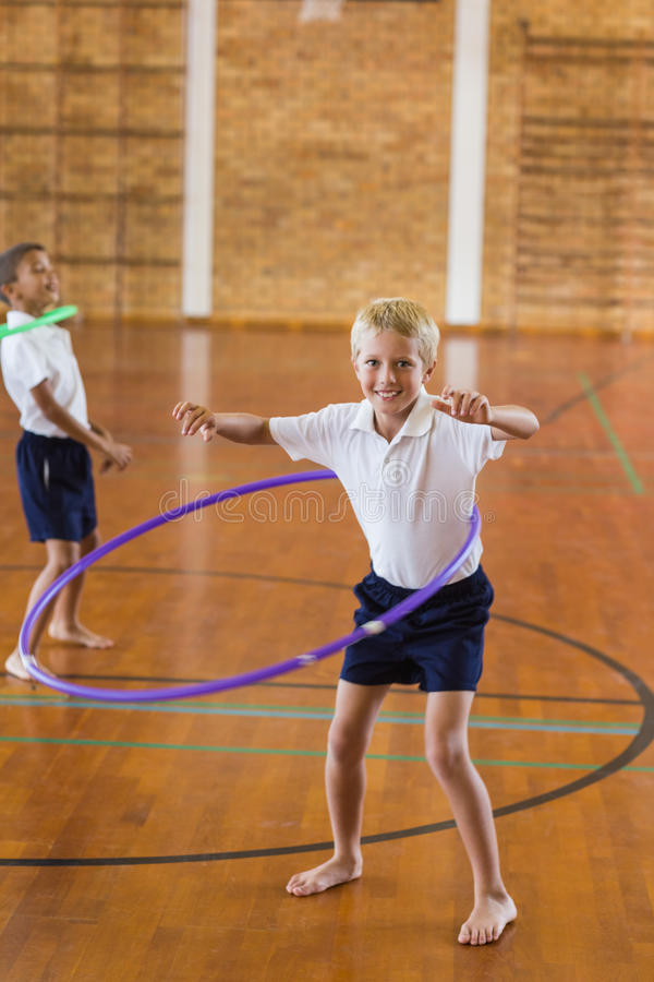 Colegial que juega con el aro del hula en gimnasio de la escuela imagen de archivo libre de regalías