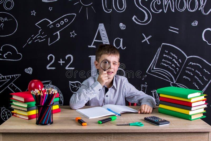 Colegial que se sienta en el escritorio con los libros, fuentes de escuela, sosteniéndose con una lupa antes del ojo pizarra fotografía de archivo libre de regalías