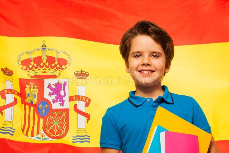 Colegial sonriente que aprende español imagenes de archivo