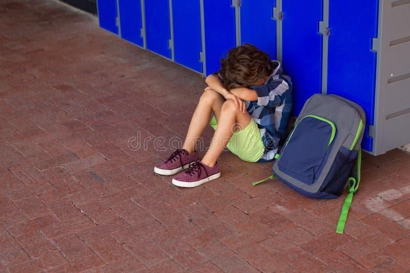 Colegial triste que se sienta solamente en piso en el vestuario foto de archivo