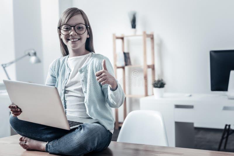 Colegiala alegre que manosea con los dedos para arriba mientras que usa el ordenador fotos de archivo