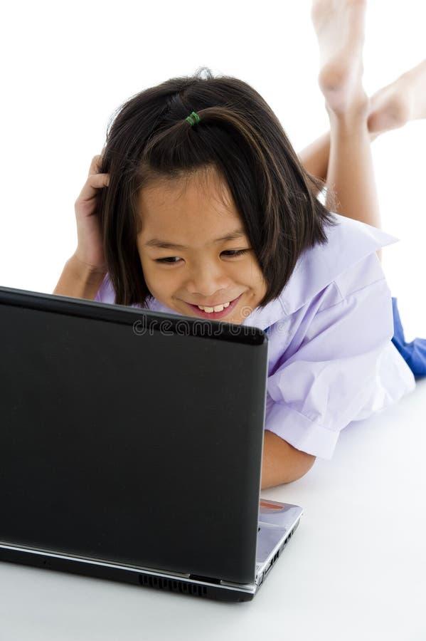 Colegiala asiática con la computadora portátil imagenes de archivo