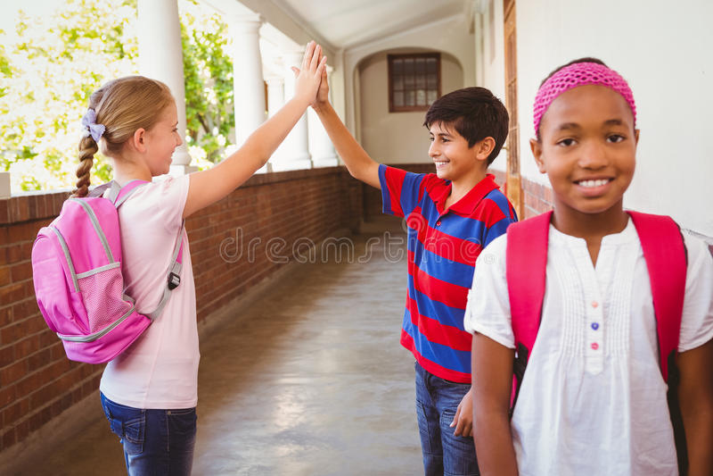 Colegiala con alto fiving de los amigos en fondo en el pasillo de la escuela imágenes de archivo libres de regalías