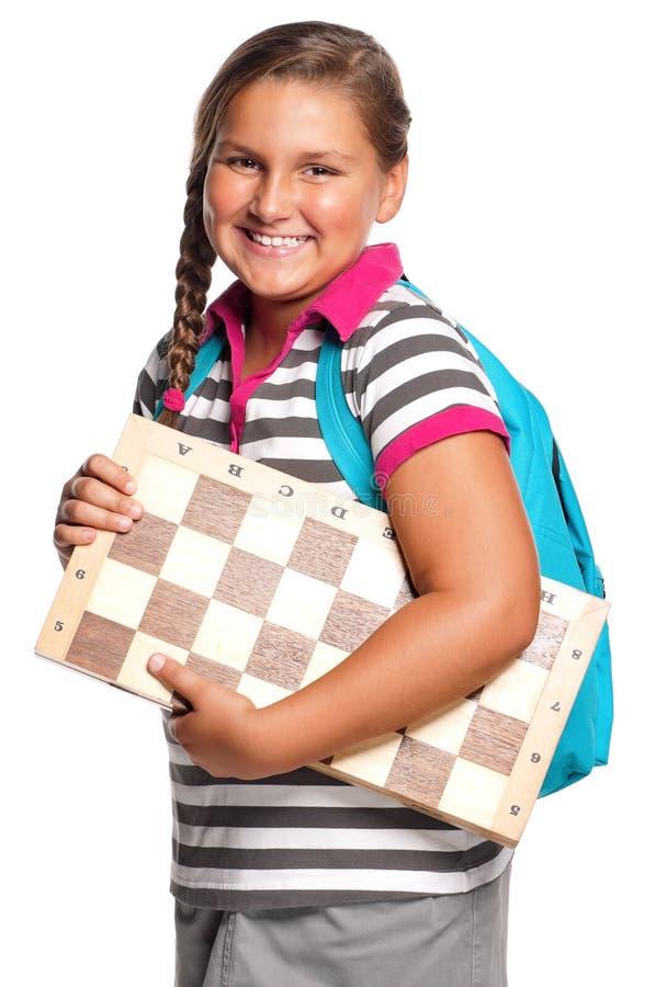 Colegiala con el tablero de ajedrez foto de archivo libre de regalías
