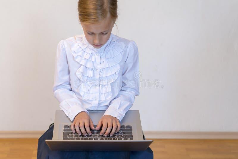 Colegiala con un ordenador portátil la muchacha hace ejercicios en un ordenador portátil De nuevo a escuela fotos de archivo