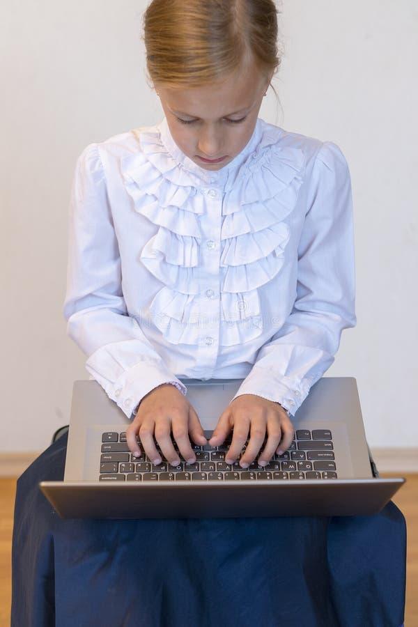 Colegiala con un ordenador portátil la muchacha hace ejercicios en un ordenador portátil De nuevo a escuela Foto vertical fotos de archivo libres de regalías