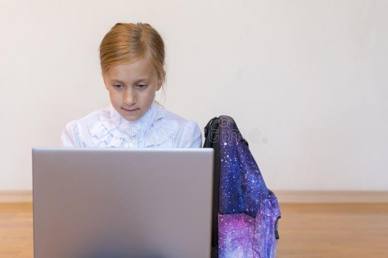 Colegiala con un ordenador portátil la muchacha hace ejercicios en un ordenador portátil Muchacha con el ordenador port?til en el imagen de archivo