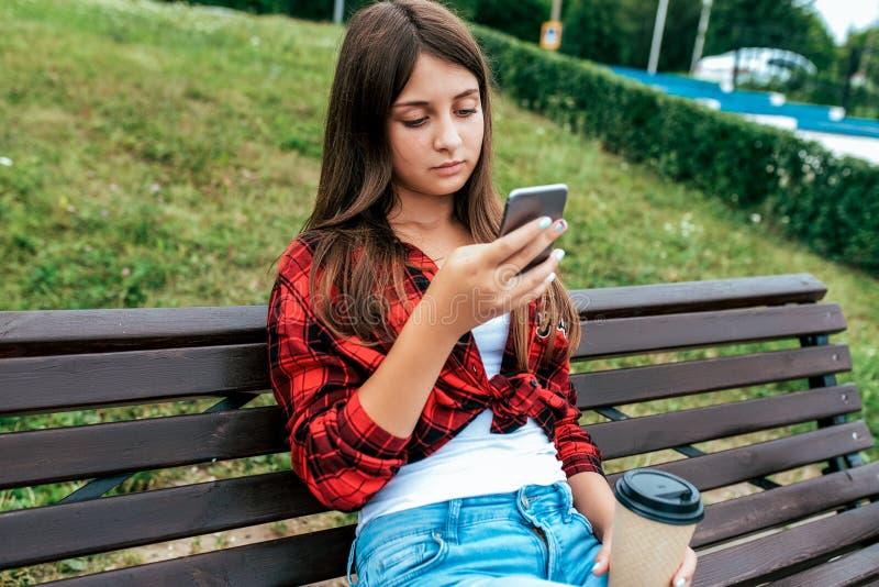 Colegiala de la muchacha 13-16 años que se sientan en un banco en su teléfono de la mano Uso en línea de la charla en las redes s fotos de archivo