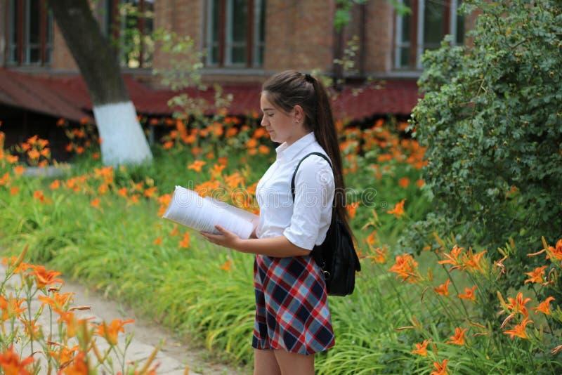 Colegiala de la muchacha con una carpeta en sus manos imagen de archivo
