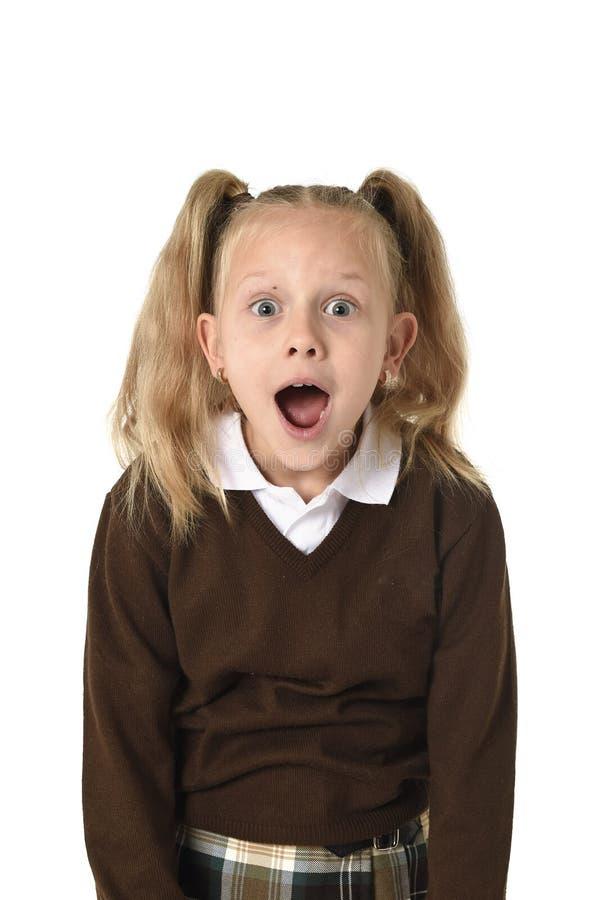 Colegiala dulce en las coletas y el uniforme escolar que parecen sorprendidos chocado y sorprendido foto de archivo