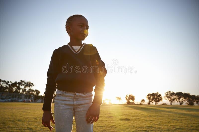 Colegiala elemental africana en un parque en la puesta del sol, cierre para arriba imagenes de archivo