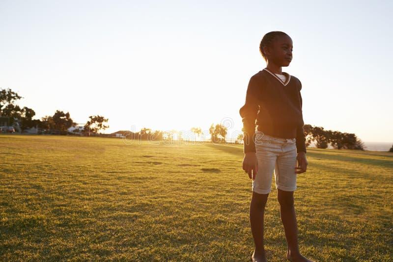 Colegiala elemental africana que se coloca en un parque en la puesta del sol imagenes de archivo