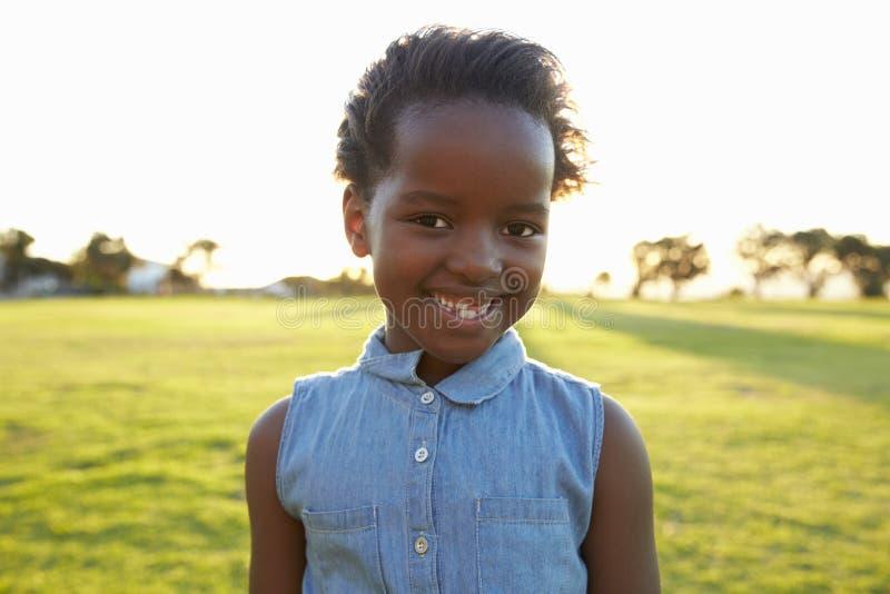 Colegiala elemental africana que sonríe en un parque, cierre para arriba fotos de archivo libres de regalías