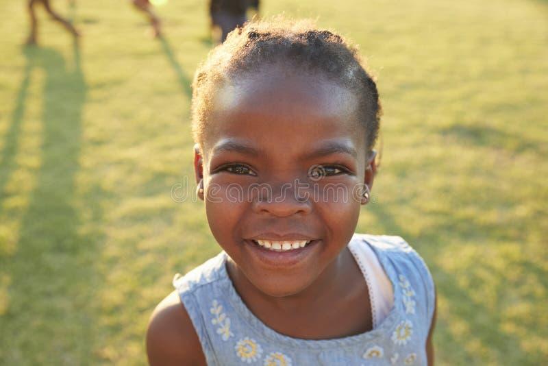 Colegiala elemental africana que sonríe a la cámara al aire libre foto de archivo libre de regalías