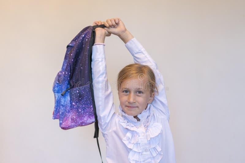 Colegiala feliz con la mochila Ni?a divertida con la mochila grande que salta y que se divierte contra la pared de la turquesa Co fotos de archivo libres de regalías