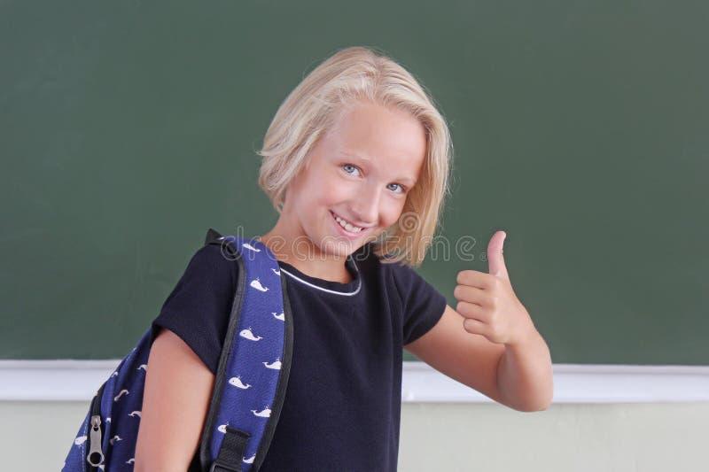 Colegiala feliz con la mochila que muestra el pulgar para arriba en una sala de clase cerca de la pizarra verde El niño le gusta  fotos de archivo