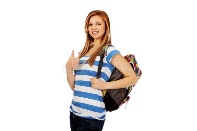 Colegiala feliz con la mochila y el pulgar para arriba imagen de archivo libre de regalías