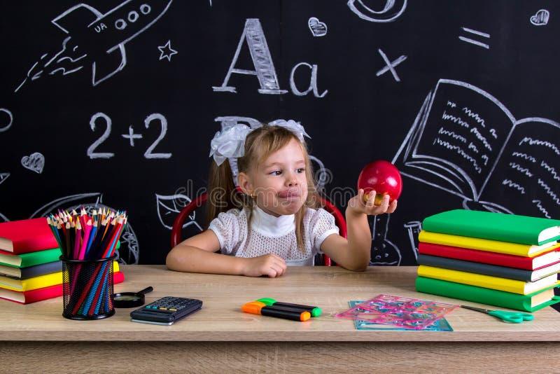 Colegiala hambrienta que se sienta en el escritorio con los libros, fuentes de escuela, sosteniéndose en su manzana roja del braz foto de archivo