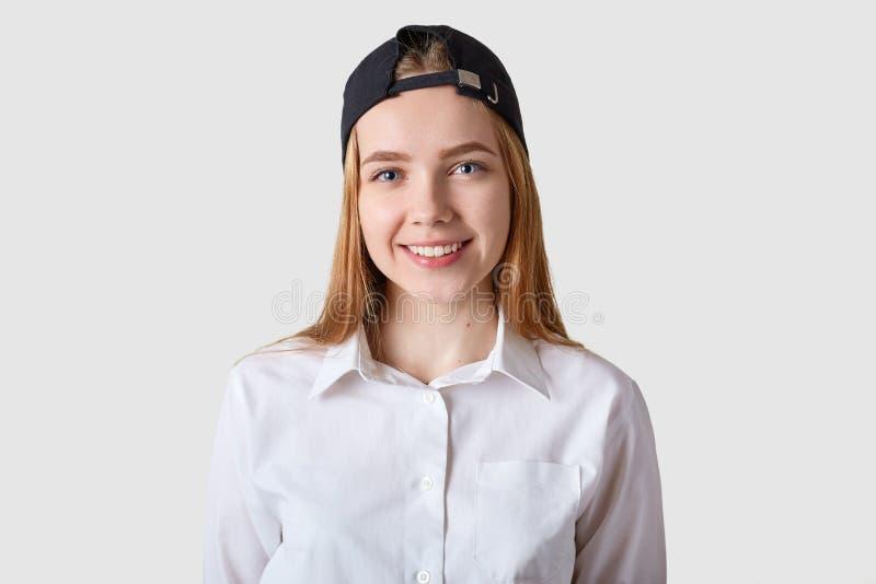 Colegiala hermosa joven que presenta en la blusa blanca Dieciocho años del adolescente que mira la cámara sobre fondo brillante d foto de archivo