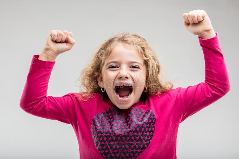 Colegiala joven de risa que aumenta las manos foto de archivo