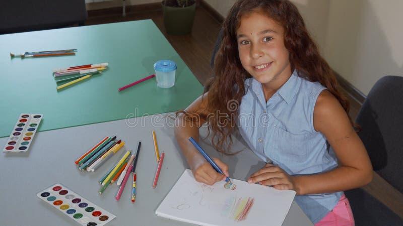 Colegiala joven que sonríe a la cámara mientras que dibuja imágenes de archivo libres de regalías