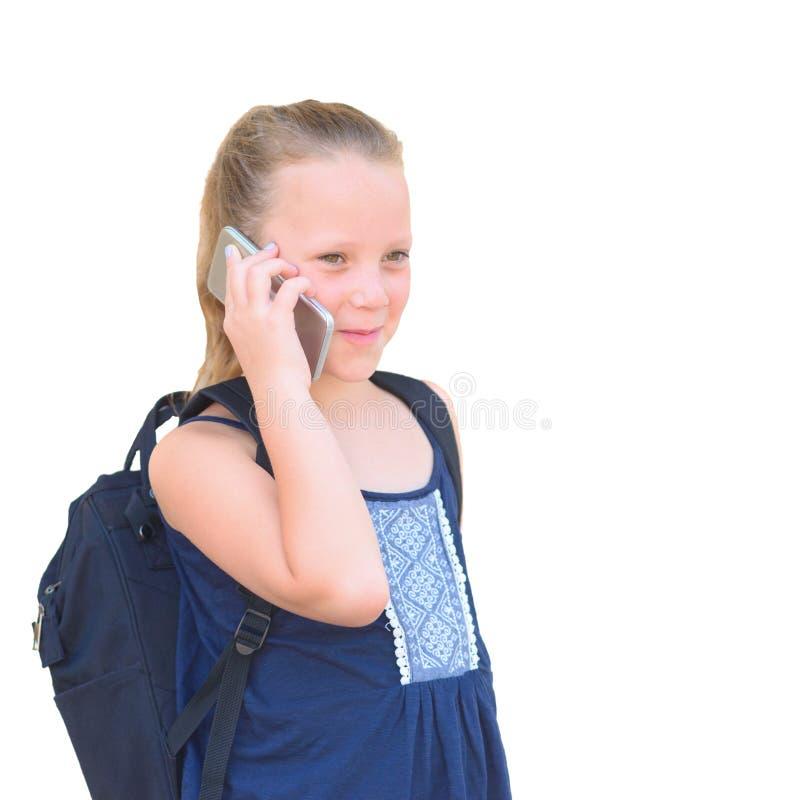 Colegiala linda con la mochila que habla en imagen aislada del teléfono celular foto de archivo
