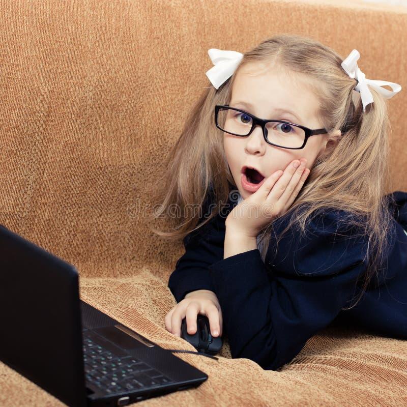 Niño con un ordenador portátil en choque. fotos de archivo
